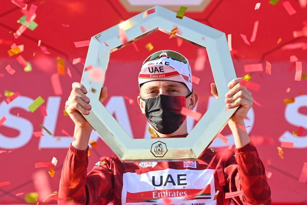 Il vincitore dell'UAE Tour stringe tra le mani il trofeo.