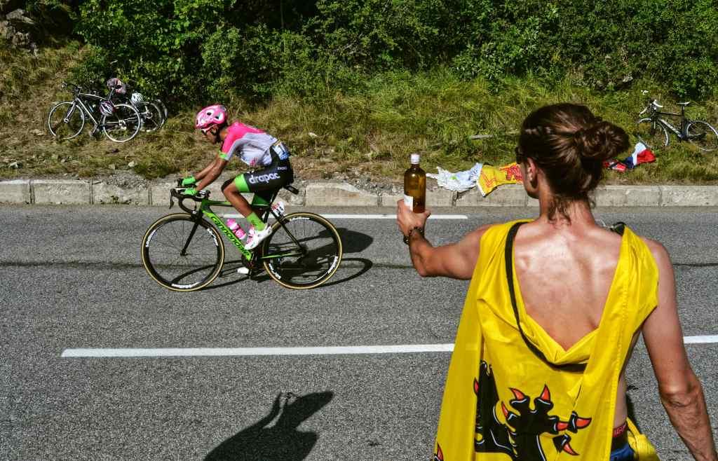 Sull'Alpe D'Huez un tifoso indossa la bandiera del Leone delle Fiandre e porge la birra ad un ciclista in azione.